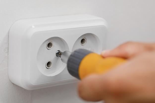 Elektryk instalujący gniazdo elektryczne