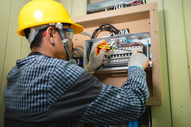 Elektryk instalujący gniazdo w nowym domu, elektryk bezpiecznie pracuje na przełącznikach i gniazdach instalacji elektrycznej w domu.