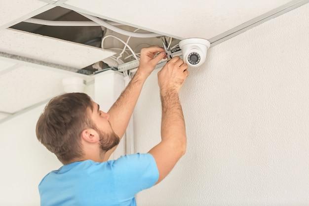 Elektryk instalujący kamerę bezpieczeństwa w pomieszczeniu