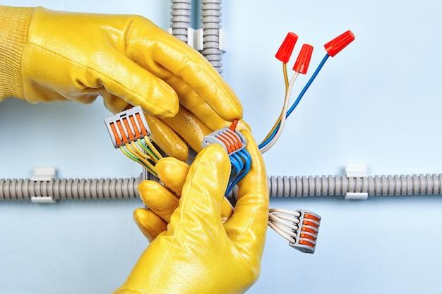 Elektryk instaluje elektryczną skrzynkę przyłączeniową z kompaktowym złączem 5-przewodowym listwą zaciskową