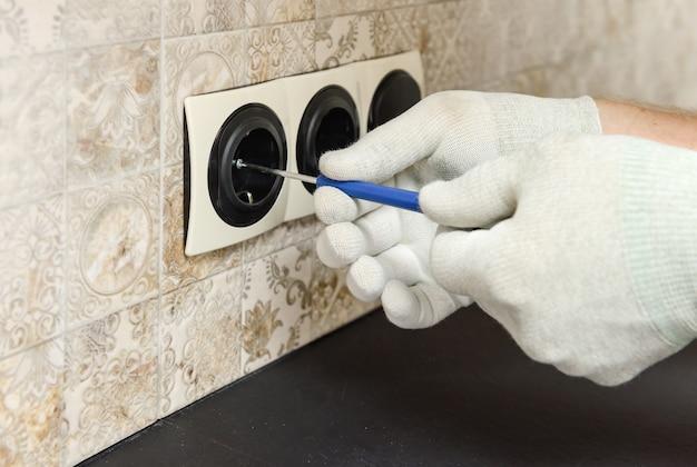 Elektryk instaluje przełączniki i gniazdka na ścianie.