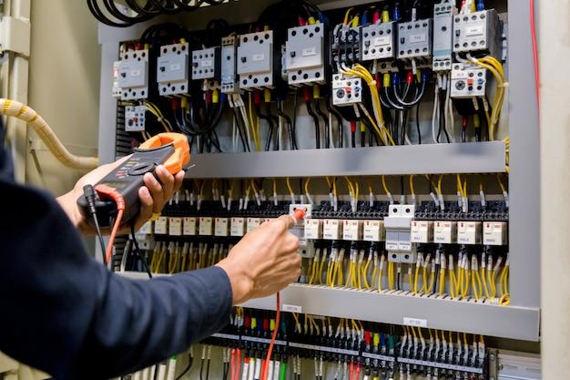 Elektryk inżynier tester pracy mierzący napięcie i prąd linii elektroenergetycznej w sterowaniu szafą elektryczną.