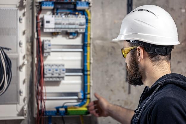 Elektryk mężczyzna pracuje w rozdzielnicy z elektrycznym kablem połączeniowym
