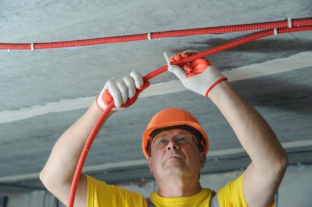 Elektryk mocujący rurkę falistą do sufitu