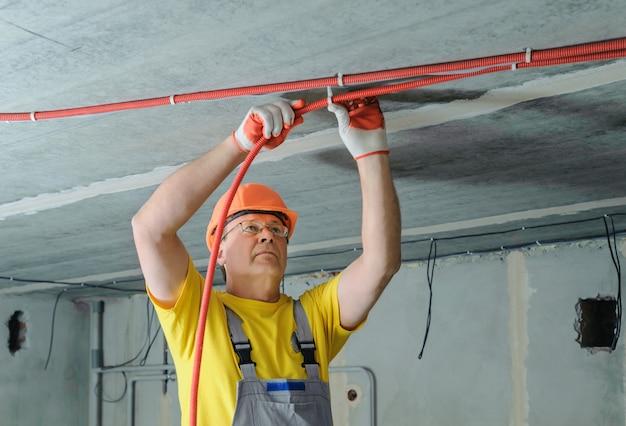 Elektryk mocuje falistą rurkę elektryczną.