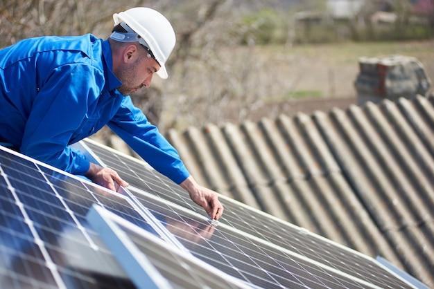 Elektryk montujący panel słoneczny na dachu nowoczesnego domu