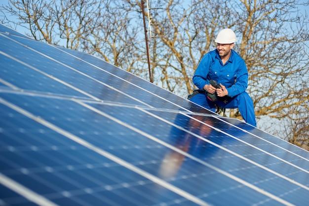 Elektryk montuje panel słoneczny na dachu nowoczesnego domu