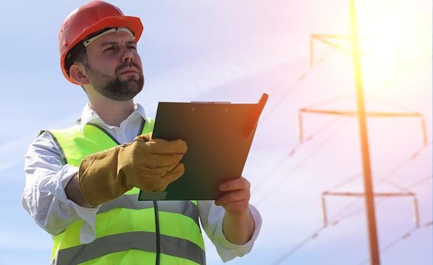 Elektryk na polach w pobliżu linii elektroenergetycznej. elektryk zarządza procesem wznoszenia linii energetycznych. mechanik w kasku i odblaskowej formie oraz w specjalnych rękawiczkach w pracy.