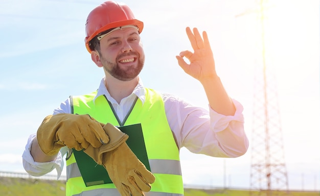 Elektryk na polach w pobliżu linii elektroenergetycznej. elektryk zarządza procesem wznoszenia linii energetycznych. mechanik w kasku i odblasku tworzą podczas pracy specjalne rękawiczki.