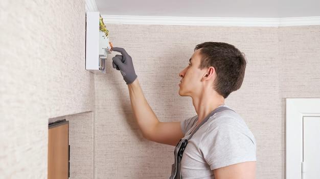 Elektryk naciska dźwignie na tablicy rozdzielczej, aby naprawić w pokoju