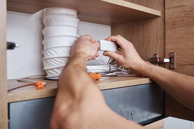 Elektryk podłącza przewód w szafce kuchennej