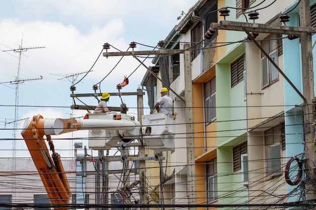 Elektryk podszedł do kosza dźwigu