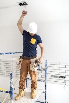 Elektryk pracownik budowlany w białym kasku przy pracy, montaż lamp na wysokości. profesjonalista w kombinezonach na miejscu naprawy.