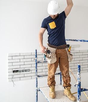 Elektryk pracownik budowlany w białym kasku przy pracy, montaż lamp na wysokości.