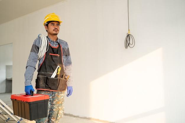 Elektryk pracujący i sprawdzający proces produkcji na budowie, inżynier, koncepcja budowy.