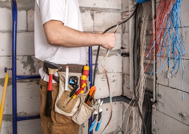 Elektryk pracujący w pobliżu tablicy z przewodami. instalacja i podłączenie elektryki.