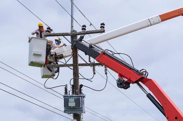 Elektryk pracuje na wózku kubełkowym do utrzymania linii przesyłowych wysokiego napięcia.
