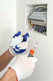 Elektryk Przycina Przewód Na żądaną Długość Podczas Instalacji Sprzętu Elektrycznego Premium Zdjęcia