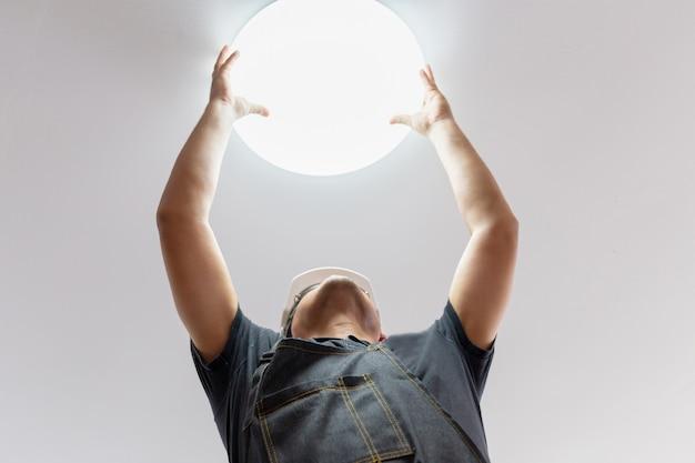 Elektryk sprawdza oświetlenie sufit w domu z białym hełmem, technika pojęcie.