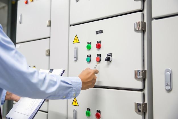 Elektryk sprawdzający instalację elektryczną centrali.