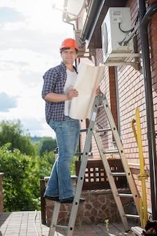 Elektryk stojący na wysokiej drabinie i trzymający plan domu
