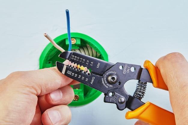 Elektryk usuwa izolację z przewodów okrągłej skrzynki elektrycznej za pomocą przecinaka do ściągania izolacji.