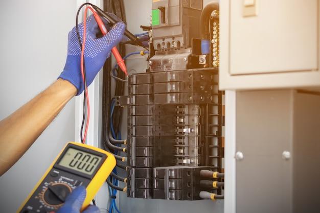 Elektryk używa miernika cyfrowego do pomiaru napięcia w szafie sterowniczej wyłącznika na ścianie.