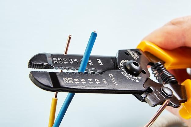 Elektryk używa przecinaka do ściągania izolacji z przewodów podczas prac elektrycznych.