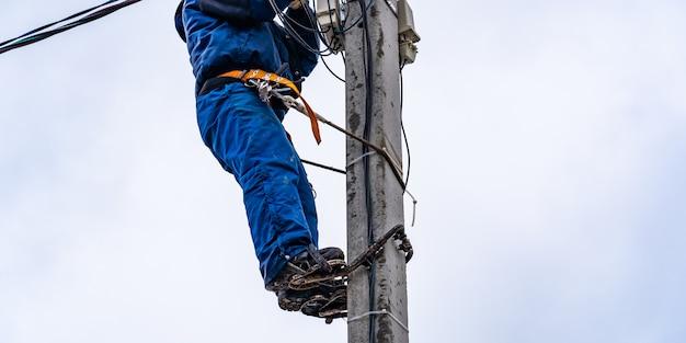 Elektryk vysotnik wykonuje instalację sieci elektroenergetycznych