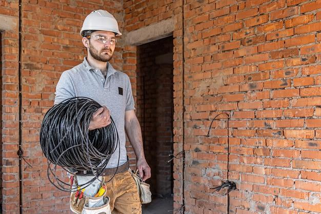 Elektryk w kasku patrzy na ścianę trzymając kabel elektryczny.