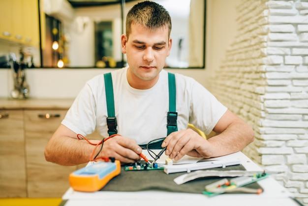 Elektryk w mundurze sprawdza chip, złota rączka. profesjonalny pracownik wykonuje naprawy wokół domu, usługi remontowe w domu