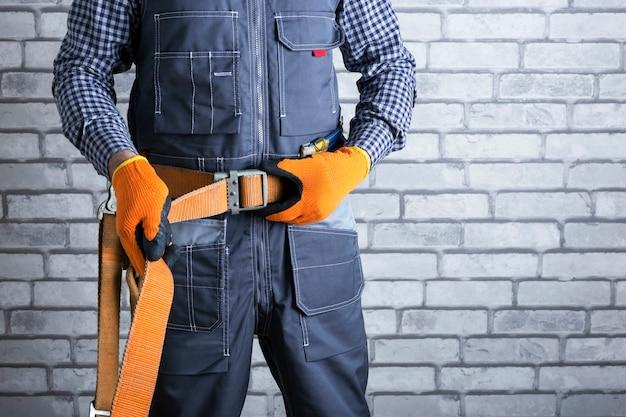Elektryk w mundurze zakłada pas bezpieczeństwa. środki ochrony osobistej bardzo ważne dla ochrony zdrowia. bezpieczeństwo w pracy.