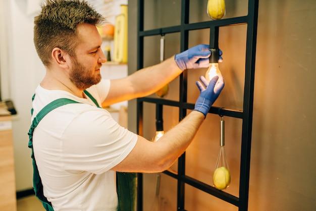 Elektryk w mundurze zmienia żarówkę, złota rączka. profesjonalny pracownik wykonuje naprawy wokół domu, usługi remontowe w domu