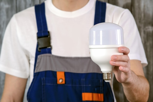 Elektryk w niebieskim kombinezonie. w dłoni trzyma potężną przemysłową żarówkę energooszczędną. pojęcie oszczędzania energii.