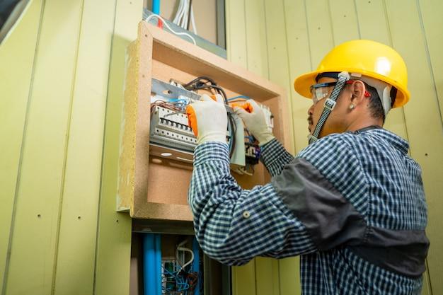 Elektryk w pracy w domu, elektryk naprawiający skrzynkę elektryczną za pomocą szczypiec w korytarzu domowego systemu elektrycznego.
