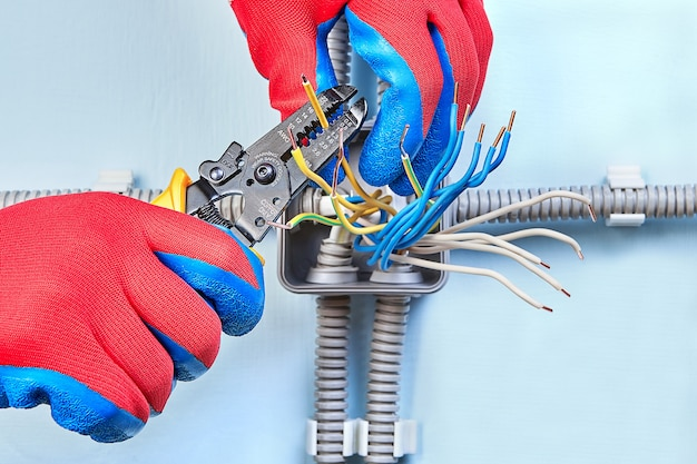 Elektryk w rękawicach ochronnych przecina miedziane przewody domowej sieci energetycznej za pomocą narzędzia do ściągania izolacji.