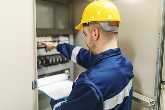 Elektryk w stroju ochronnym i kasku, trzymając schowek i próbując naprawić usterkę, stojąc obok deski rozdzielczej w zakładzie przemysłu ciężkiego.