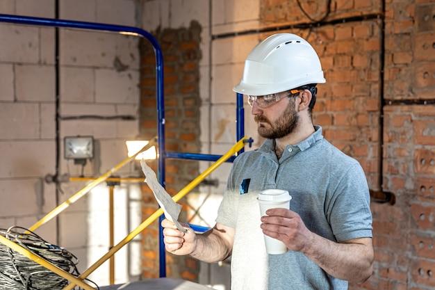 Elektryk z kawą w ręku studiuje rysunek konstrukcyjny