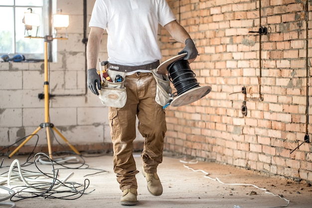 Elektryk z narzędziami, pracujący na budowie. koncepcja naprawy i złota rączka.