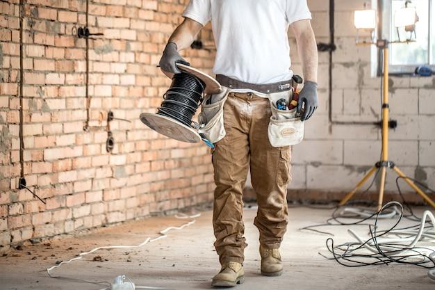 Elektryk z narzędziami, pracujący na budowie