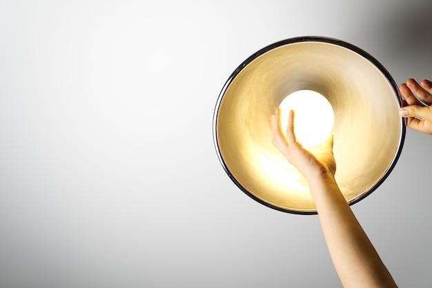 Elektryk zakończył montaż lampy sufitowej