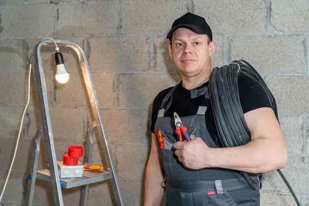 Elektryk ze zwojem przewodów na ramieniu stoi trzymając szczypce