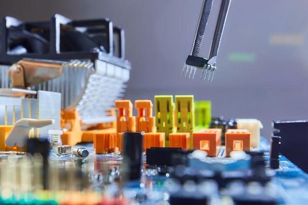 Elektryka mężczyzna naprawia mikroelektroniczną deskę trzyma mikroukład