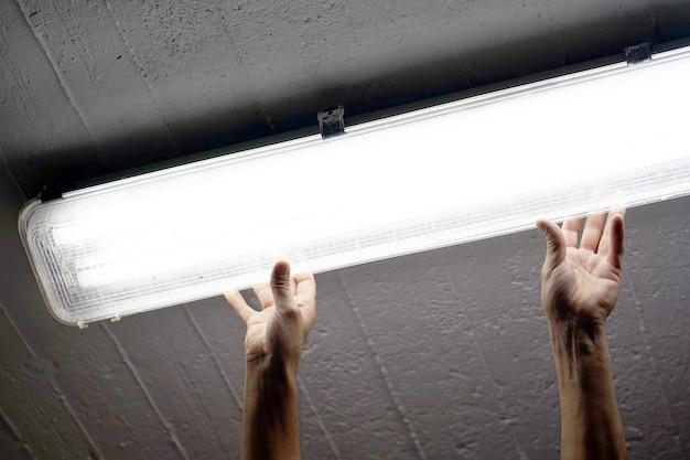 Elektryka mężczyzna pracownik instaluje fluorescencyjną lampę
