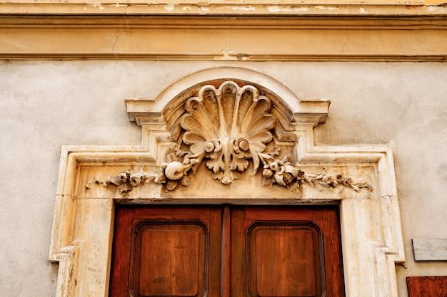 Element architektoniczny nad wejściem, wykonany w stylu płaskorzeźby.