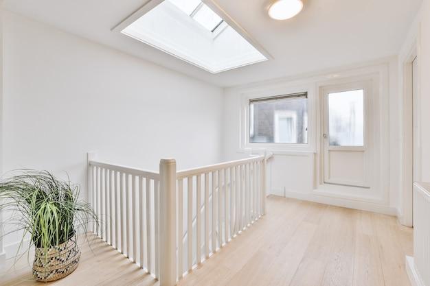 Element schodów z białymi ozdobnymi tralkami i drewnianymi balustradami w mieszkaniu w stylu vintage