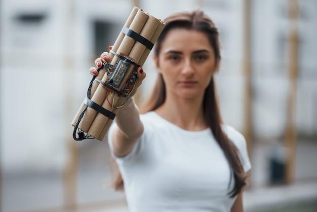 Elementy cyfrowe. pokazuje bombę zegarową. młoda kobieta trzyma w ręku niebezpieczną broń wybuchową