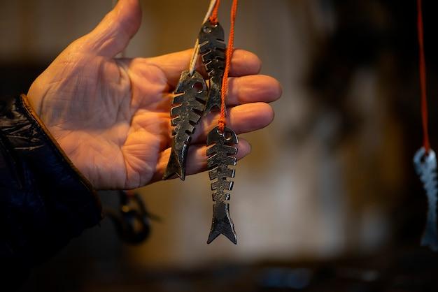 Elementy ozdobne kowala metalowe rybki wiszące w kuźni, warsztat. ręcznie robione, kunszt i koncepcja kowalstwa