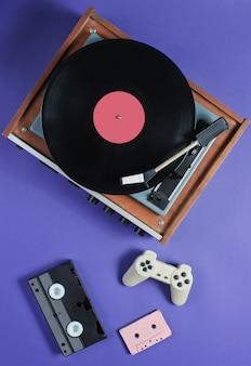 Elementy retro z odtwarzaczem winylu, taśmami audio i wideo oraz gamepadem
