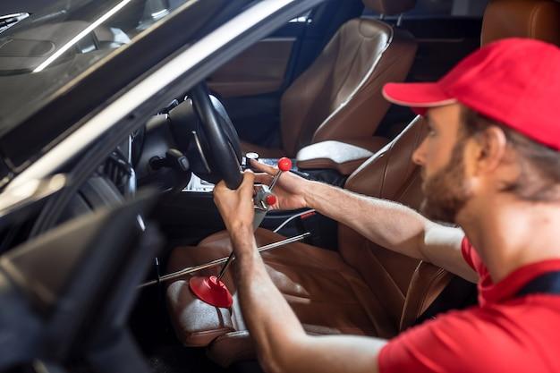 Eliminacja awarii samochodu. mężczyzna w czerwonej czapce naprawiający samochód trzymający kierownicę przykucnął w pobliżu otwartych drzwi